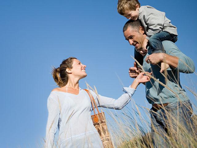 Mutter schaut lächelnd ihren Mann an, der sein Kind auf den Schultern trägt