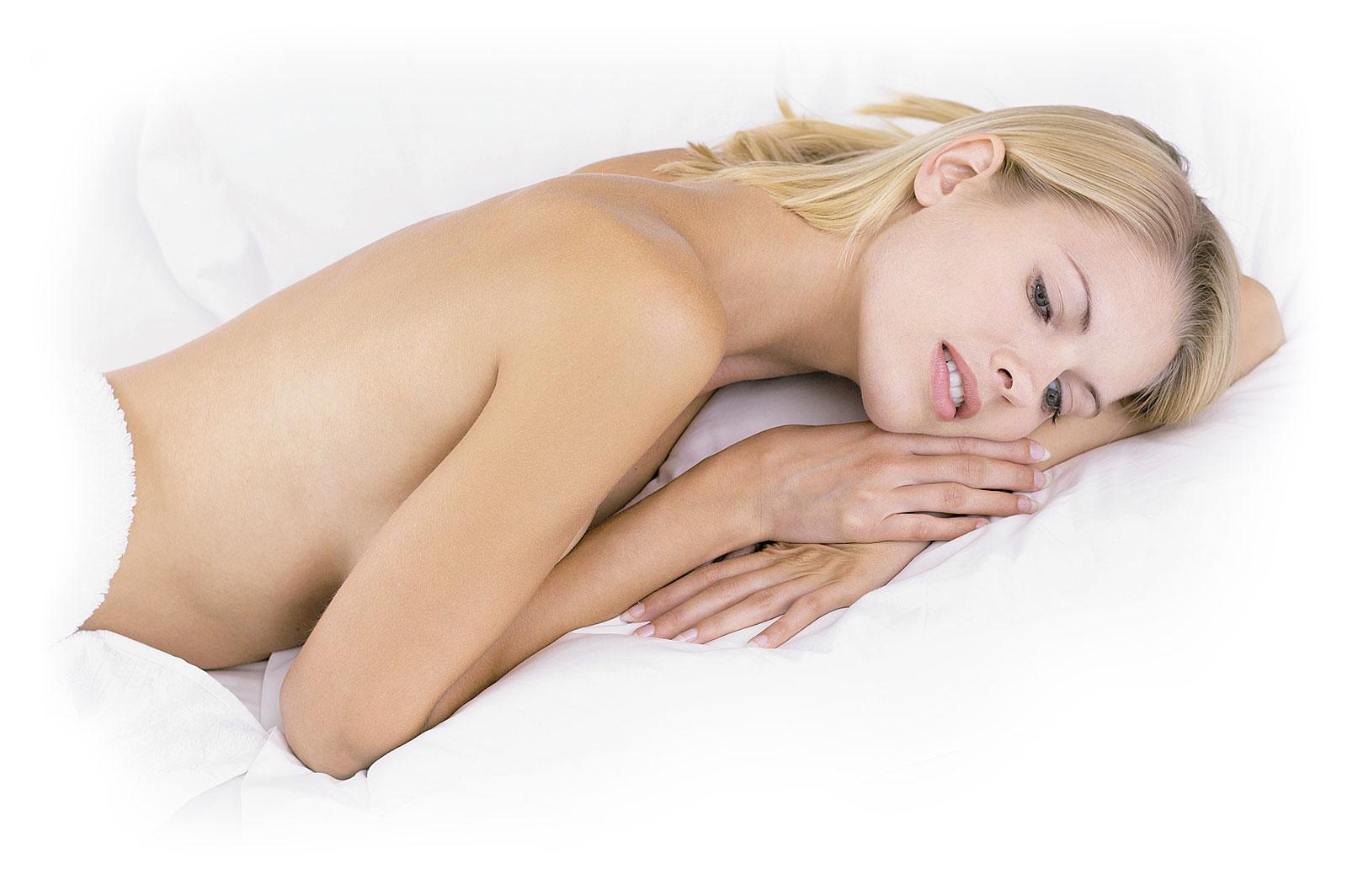 Frau mit blonden Haaren liegt nackt, jedoch verdeckt, in einem Bett mit weißer Bedecke und weißen Laken