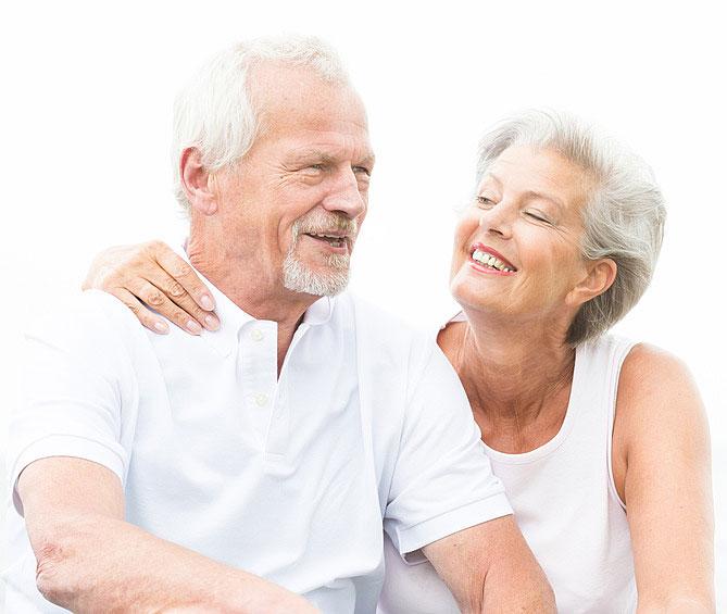 Ein älterer Herr und eine ältere Frau, beide mit einem weißen Shirt lachen gemeinsam