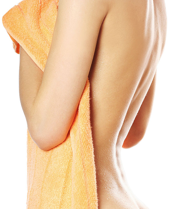 Nackte Frau, vorne nur mit einem Handtuch bedeckt, zeigt ihren Rücken